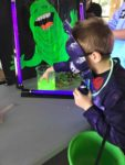 boy in Halloween costume wearing a purple mask touching green slime