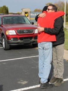 man in red jacket hugging man in black jacket in parking lot front of red Ford Explorer