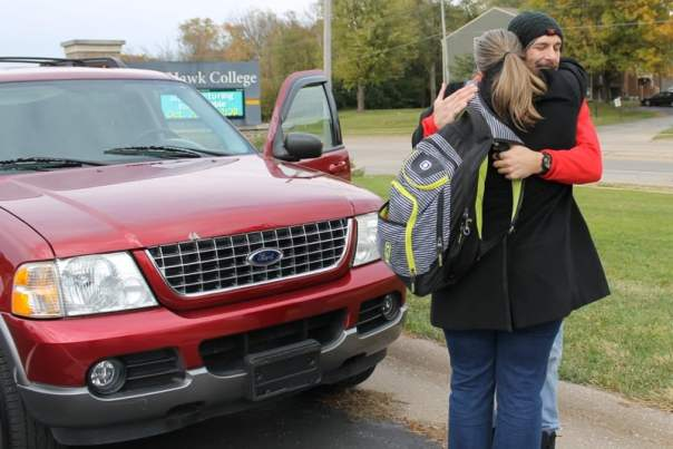 Red Ford Explorer in parking lot with man and woman hugging in front of it