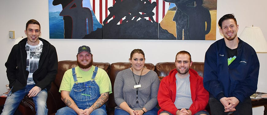Four veteran students pose on couch in veterans center