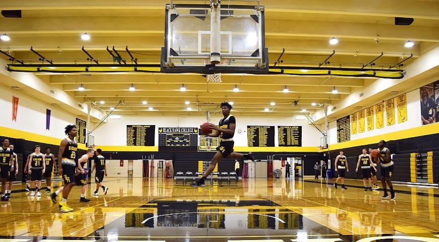 Men's basketball player slam dunks the ball