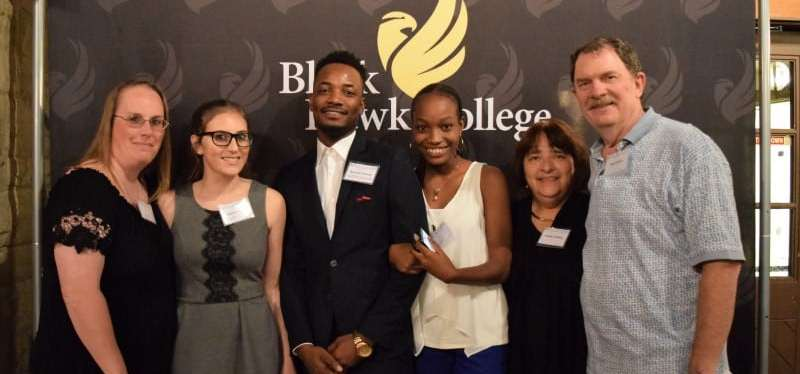 scholarship event attendees smile in front of backdrop with BHC logo