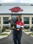 student holding BHC sign standing in front of a stadium