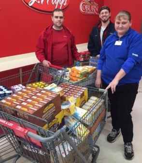 2 men & 1 woman in store with 3 carts of groceries