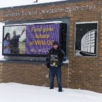 student holds BHC sign in front of Western Illinois University signage