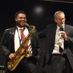 student with saxophone laughs while professor tells a story during a concert