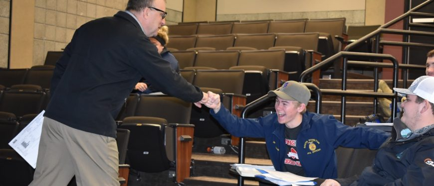 Professor fist bumping student in classroom at East Campus