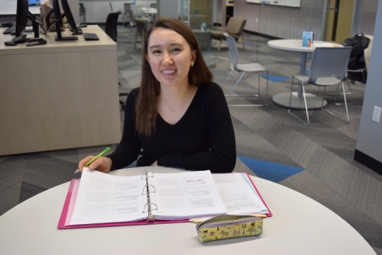 student sitting at table and smiling while turning a page in her binder