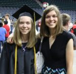 smiling female grad wearing gold cords posing with sister