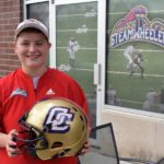 woman holding a football outside of the Quad City Steamwheelers office