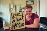 woman leaning on counter holding a sign that reads love what you do