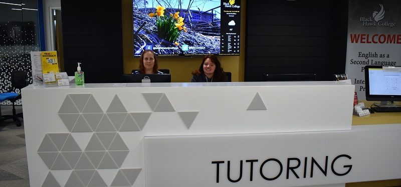 two employees sitting at a large white desk that says Tutoring