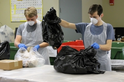 students wearing protective masks and gloves sort through trash