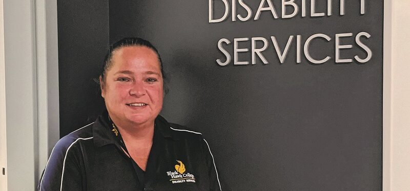 employee wearing Black Hawk College polo stands next to Disability Services entrance