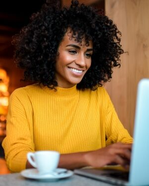 coffee cup and smiling woman working on laptop