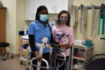 two physical therapist assistant students with a walker in a classroom
