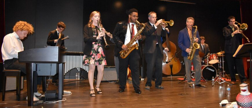 8 jazz musicians on stage playing various instruments