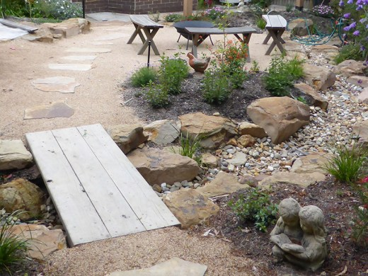 Blackburn dry creek bed with timber bridge and rocks.