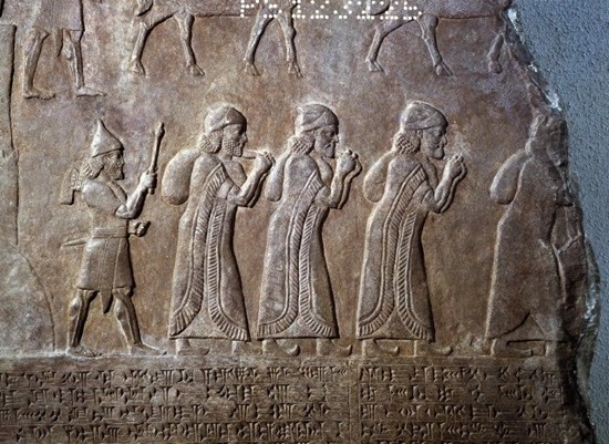 Assyrian relief showing prisoners carrying bags over shoulders