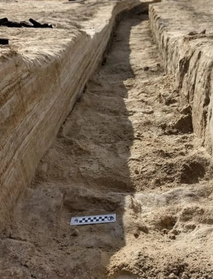 A trench dug into the brown gypsum soil on a lake playa in White Sands National Park