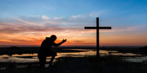 a man with the sunset behind him kneeling by a cross. ** Note: Visible grain at 100%, best at smaller sizes