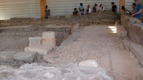 This photo shows some of the mosaic floor. A pillar of the synagogue and the Magdala Stone can be scene on the left-center.