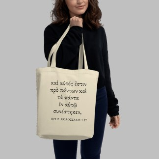 Oyster-colored bilingual tote bag with Biblical Greek (Colossians 1:17) held by woman