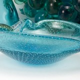 This vintage Italian glass ashtray features dimensional bubbles and real gold veils encased in aqua blue and colorless glass.