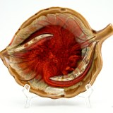 Leaf ashtray in wood-like pottery with wild fiery orange glaze in the center.