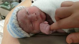 newborn wearing a hat and clutching a finger - birth in a time of Covid-19