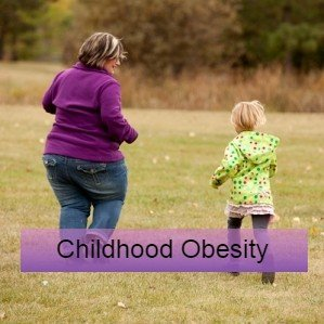 A mum and child play in a field - childhood obesity research and guidelines
