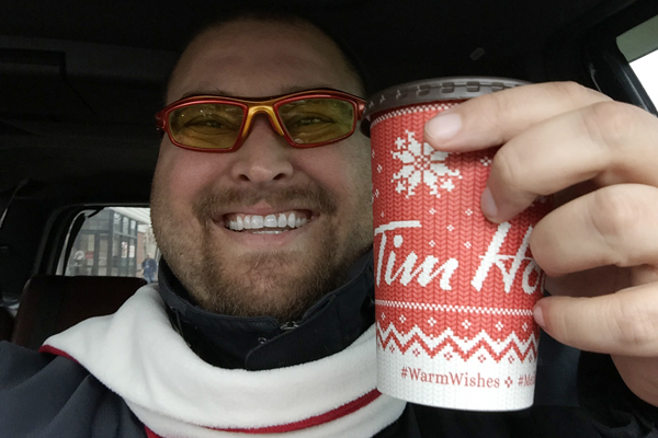 warm wishes craig holding red cup in car