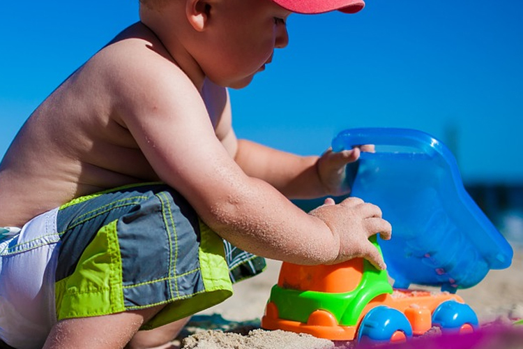 small toddler coordinating through sand play