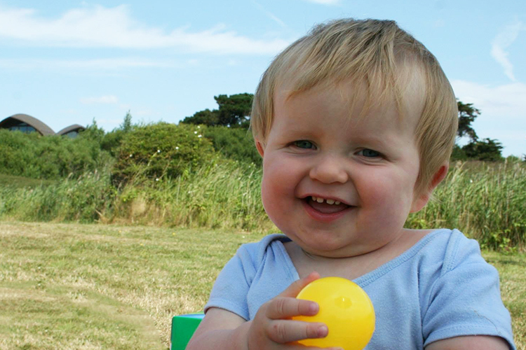 toddler group game holding coloured ball