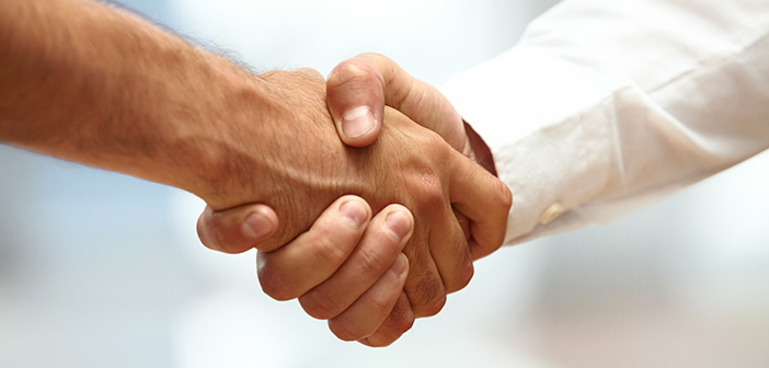 closeup of two men shaking hands indicating partnership