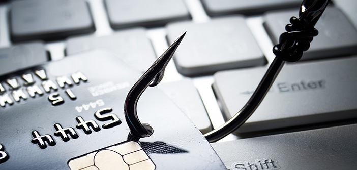 fishing hook pierced through credit card with blurred keyboard in background implying phishing scam