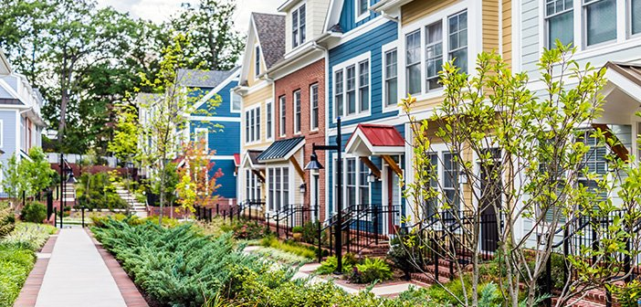 Row of colorful, red, yellow, blue, white, green painted residential townhouses, homes, houses with brick patio gardens in summer