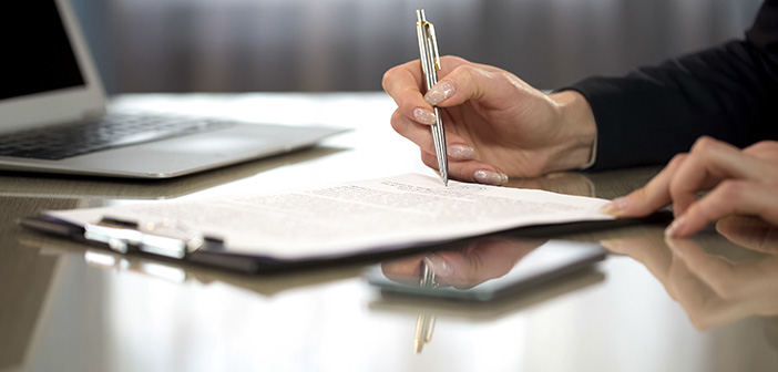 Woman in suit reading terms and conditions of agreement, signing contract, stock footage