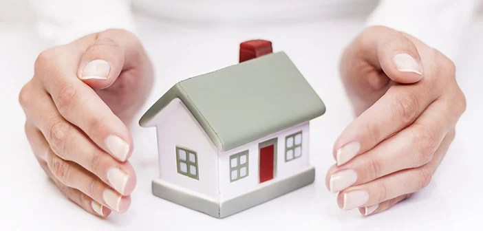 close up of small toy home with hands shielding both sides of it implying insurance coverage