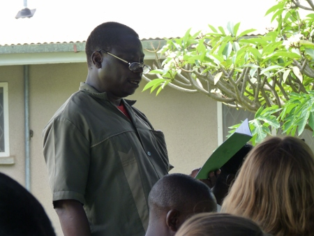 Mchungaji Julius Lukafuba leest voor uit de Zinza-vertaling