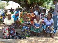 Lokale vrouwen luisteren naar de wat voorgelezen wordt