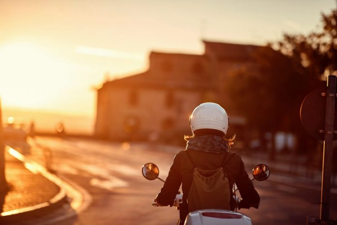 Young woman riding moped on road into sunset