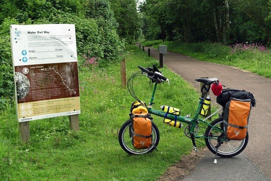 Pocket llama folding bike waits at sign on UK ride