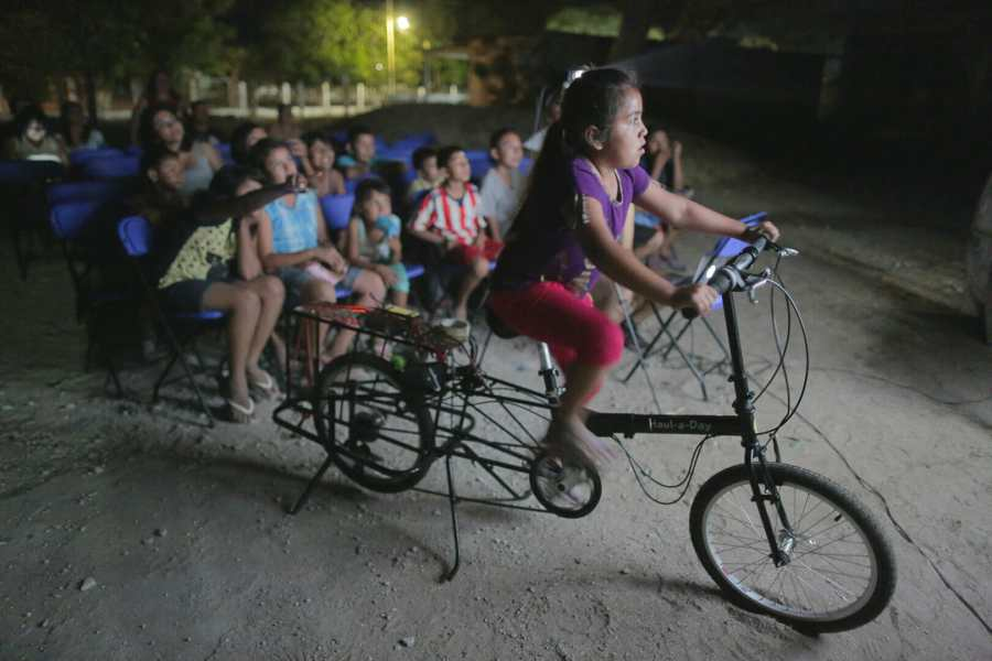 A girl pedals to generate electricity for a movie projector as her family watches