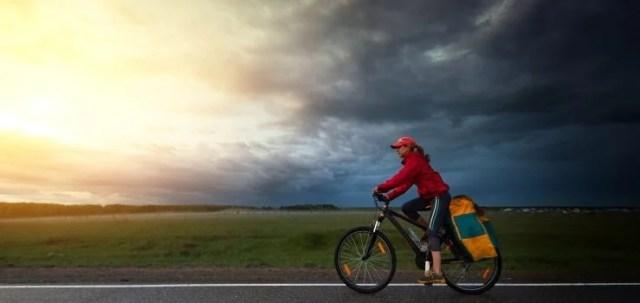 mujer en bicicleta bajo un cielo nublado