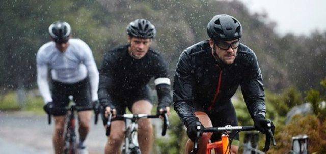 tres hombres en bicicleta bajo la lluvia