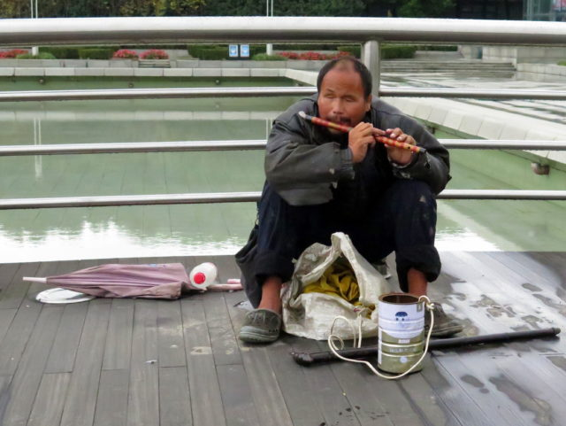 """I didn't realize this man was blind until I bent down to put some change in his can. I worried that someone would steal it, but he seemed to be okay. He will play a tune for us as we bid adieu (well, """"zaijian"""", actually) to Shanghai. Pudong, Shanghai, China, Asia."""