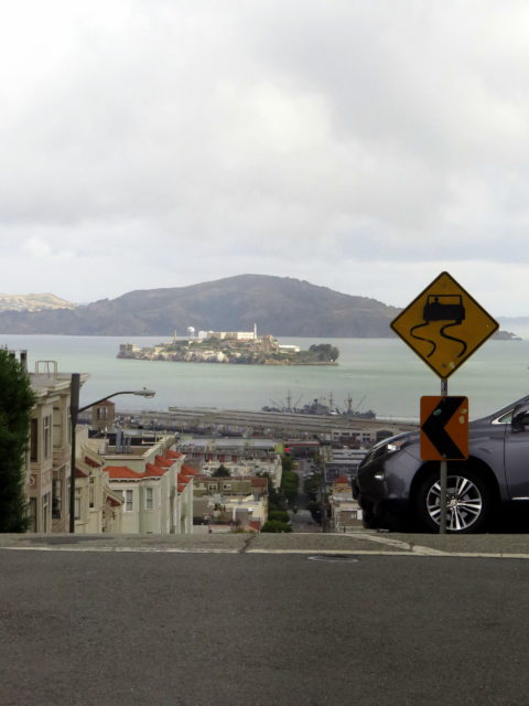"""Slippery When Wet? I'd be more concerned that the road disappears from view! Speaking of views, there's Alcatraz out in the bay. You can't escape from it. Alongside the pier is the USS """"Jeremiah O'Brien"""", explored on Day 1. San Francisco, United States, North America."""