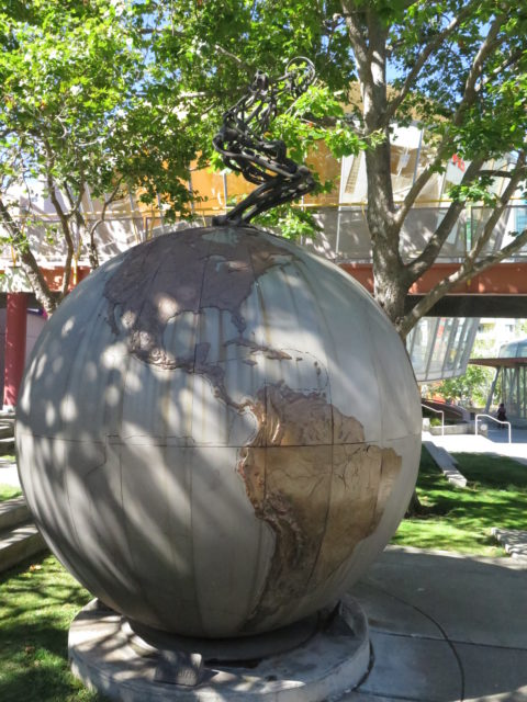 """The figure at the top of """"Urge"""" by Chico MacMurtrie appears to be about to ski down the globe. You can manipulate the figure's posture using a control at a nearby bench. San Francisco, United States, North America."""