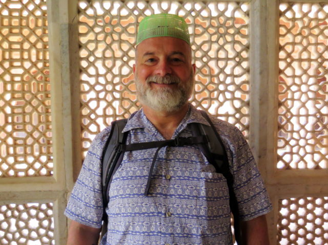 It looks like I'm wearing a bread basket on my head (and I actually might be), but it's to cover my head inside a very holy tomb at the mosque. Fatehpur Sikri, Agra, India, Asia.